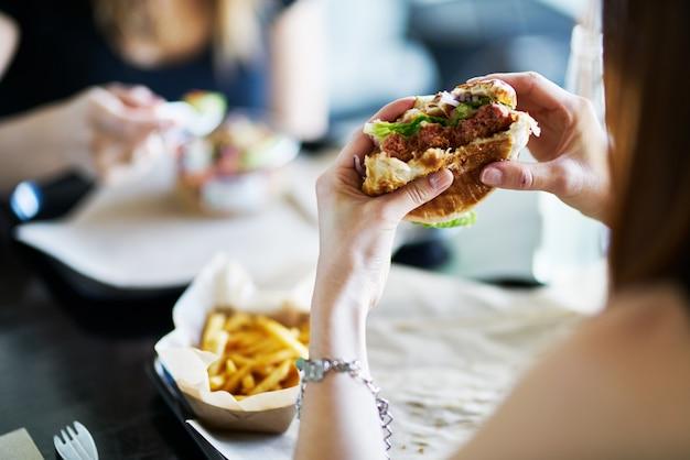 Donna che mangia mangiare hamburger senza carne vegano nel ristorante Foto Premium