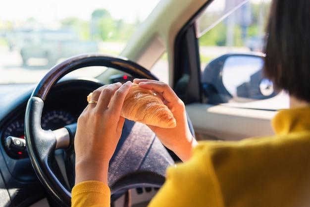 Donna che mangia cibo un fast food mentre si guida l'auto