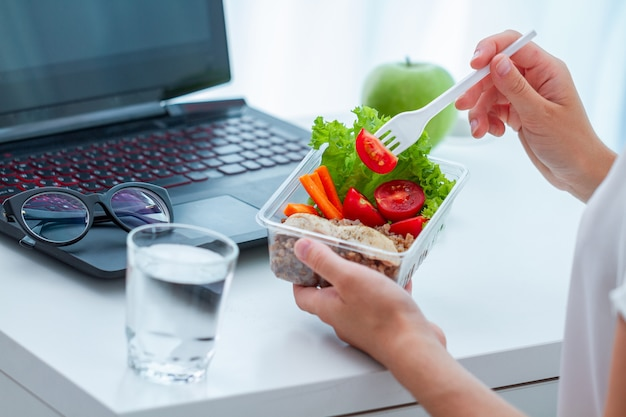 La donna che mangia l'alimento da porta via la scatola di pranzo nel luogo di lavoro durante la pausa pranzo. contenitore per alimenti al lavoro
