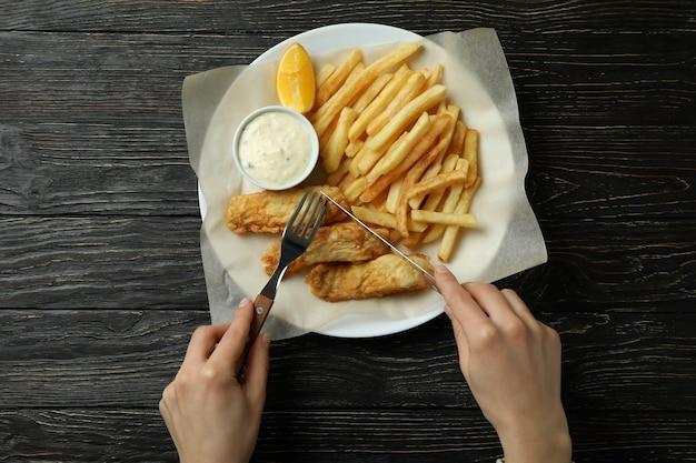 Donna che mangia pesce fritto e patatine fritte in legno, vista dall'alto