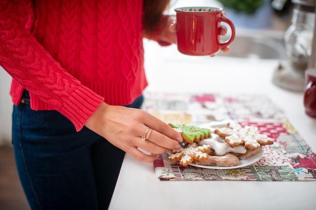 Donna che mangia i biscotti del pan di zenzero e che beve caffè