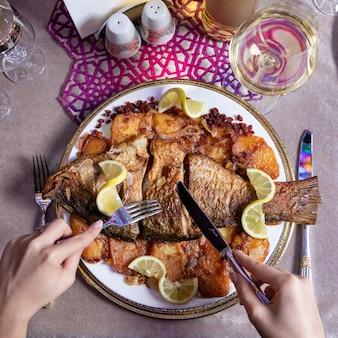 Donna che mangia un pesce intero alla griglia con una vista dall'alto di limone