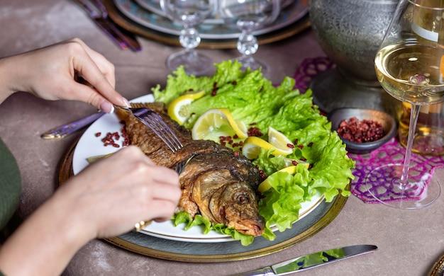 Donna che mangia un pesce intero alla griglia con un limone