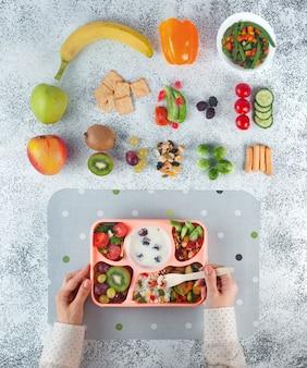 Donna che mangia un pranzo dalla scatola di pranzo vicino agli ingredienti su fondo grigio