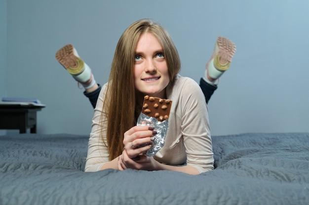 Donna che mangia cioccolato al latte con le noci intere
