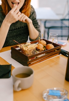 Donna che mangia mini hamburger e patatine fritte