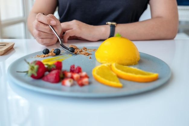 Una donna che mangia torta all'arancia con frutta mista da un cucchiaio nella caffetteria