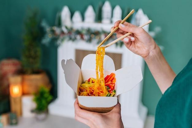 Donna che mangia le tagliatelle del wok dei frutti di mare con le bacchette dalla scatola su fondo giallo, primo piano.