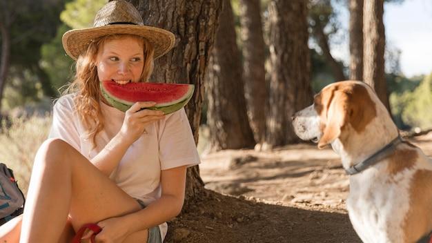 Donna che mangia una fetta di anguria vista frontale