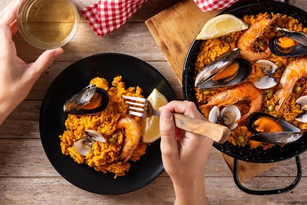 Donna che mangia la paella spagnola dei frutti di mare sulla tavola di legno