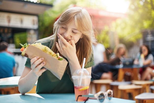Donna che mangia taco sorridente. donna bionda lentigginosa affamata che mangia cibo spazzatura in una food court a bere limonata