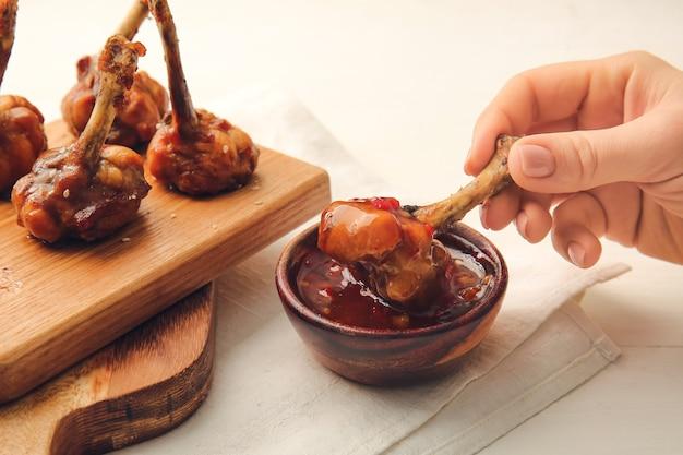 Donna che mangia gustosi lecca-lecca di pollo con salsa sulla superficie in legno chiaro