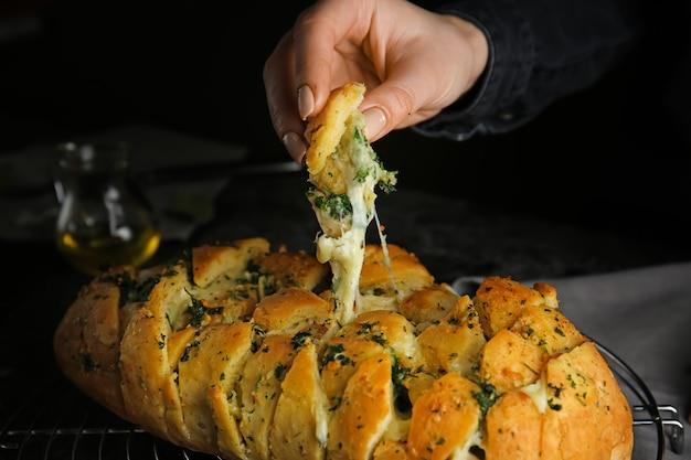 Donna che mangia pane gustoso all'aglio, primo piano