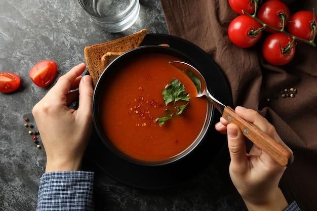 Donna che mangia una gustosa zuppa di pomodoro su oscurità