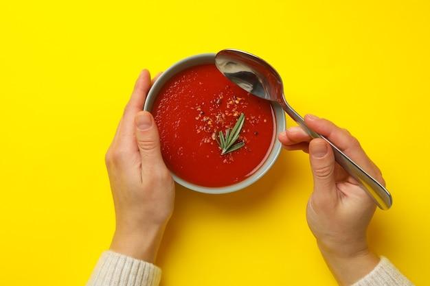 Donna che mangia zuppa di pomodoro gustosa su colore giallo