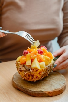 Donna che mangia una gustosa macedonia di frutta tropicale in mezza ciotola di ananas. bacche lamponi ananas mandarini arance in insalata di frutta da dessert nella caffetteria. mix di frutta alimentare servita su tagliere.