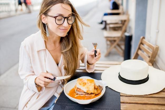 Donna che mangia il tradizionale panino portoghese con carne chiamata francesinha seduto al ristorante nella città di porto, portugal