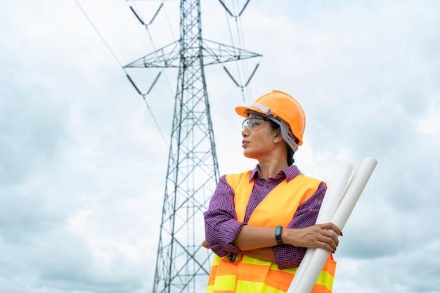 Ingegnere elettrico della donna che lavora sui progetti elettrici di progetto.