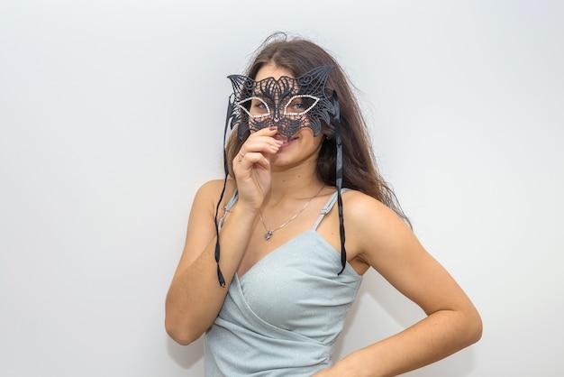 Donna in elegante abito da sera che si prepara per il travestimento, tenendo la maschera. festa di capodanno