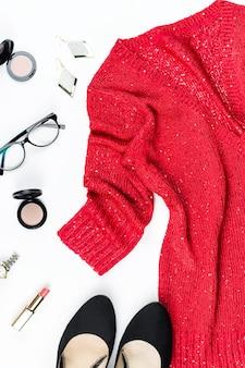 Elegante abito da donna con paillettes rosso, gioielli, trucchi e tacchi neri. disteso