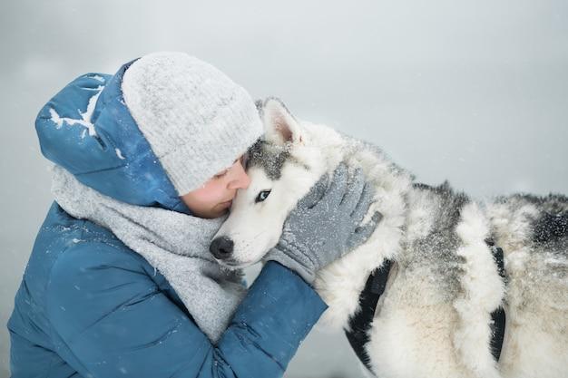 Donna che abbraccia snowy siberian husky in inverno