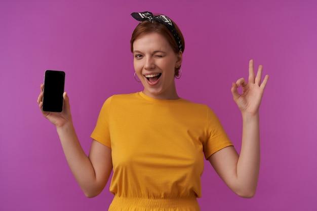 Donna emozione faccia sorridente che ti sorride e fa l'occhiolino con le braccia tenere il telefono e le dita ok in posa sul muro viola che indossa una maglietta gialla e bandana nera