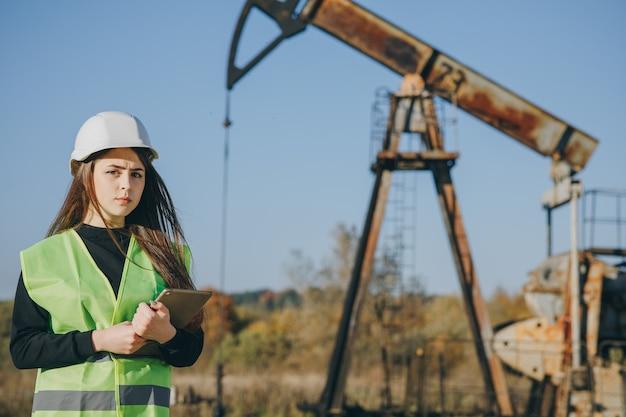 L'ingegnere della donna in elmetto protettivo sta utilizzando un computer tablet. l'ingegnere di petrolio dell'industria femminile work work sulla tavoletta digitale guarda fuori campo pompa olio