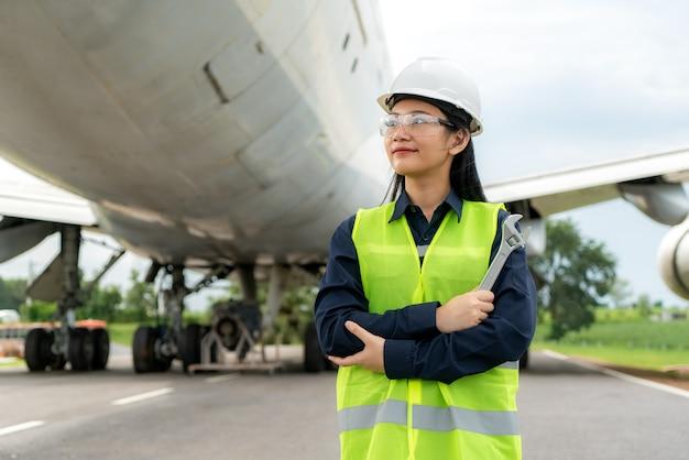Donna ingegnere manutenzione aereo braccio incrociato