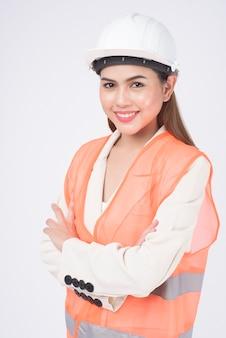 Un ingegnere donna che indossa un casco protettivo su sfondo bianco studio