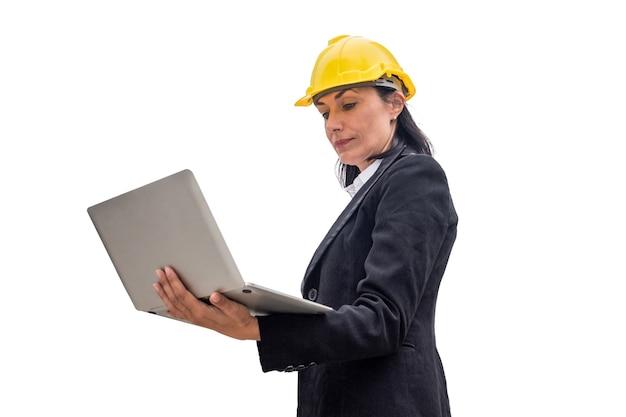 Assistente tecnico della donna con il computer portatile della tenuta del casco giallo sulla città