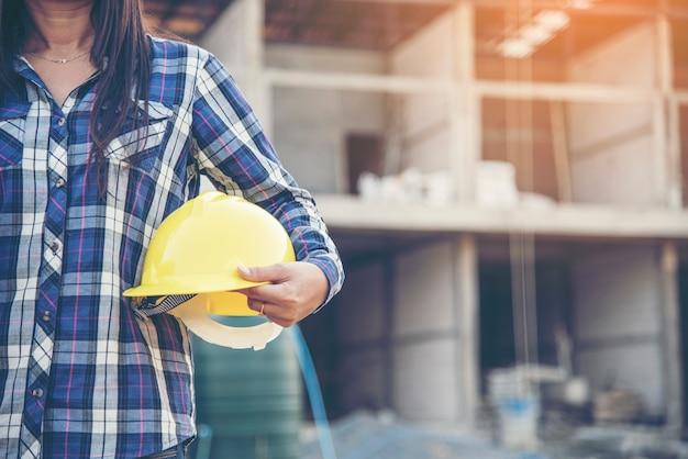 Ingegnere della donna che lavora sul cantiere e che tiene la protezione della testa del casco di sicurezza del cappello duro giallo all'industria manifatturiera. concetto di costruzione.
