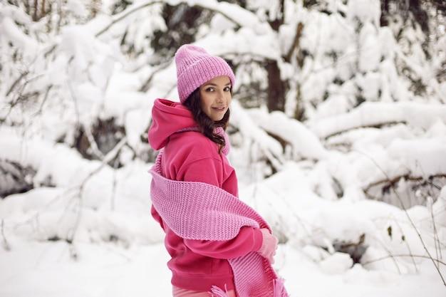 La donna gode in abiti rosa, una giacca, una sciarpa lavorata a maglia e un cappello, si trova in un bosco innevato in inverno