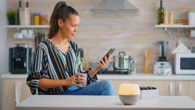 Donna che si gode l'aromaterapia con un diffusore di oli essenziali che lavora mentre beve il caffè. aroma salute essenza, benessere aromaterapia casa spa fragranza tranquilla terapia, vapore terapeutico, guarigione mentale