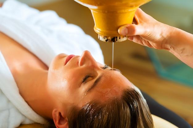 Donna che gode di un massaggio con olio ayurvedico