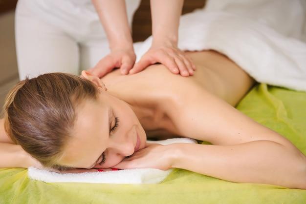 Donna che gode del massaggio classico del collo e delle spalle