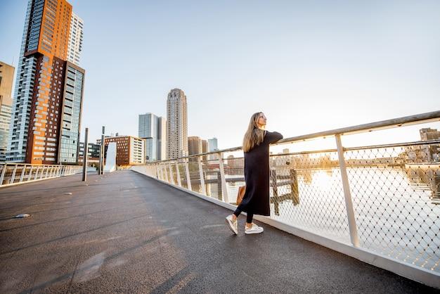Donna che gode della vista del paesaggio urbano moderno in piedi sul ponte durante la mattina nella città di rotterdam