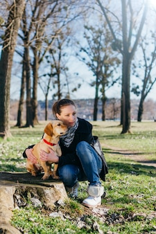 Donna che gode nel parco con un cane