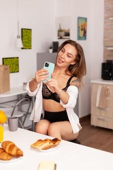 Donna che gode prendendo selfie nella cucina di casa utilizzando lo smartphone. seducente donna con tatuaggi utilizzando il telefono indossando biancheria intima temping al mattino.
