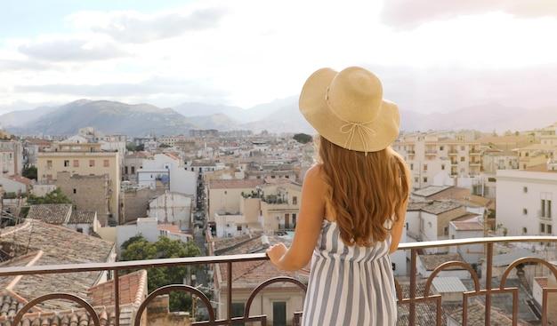 La donna gode della vista del paesaggio urbano di palermo da una terrazza sul tetto, italia