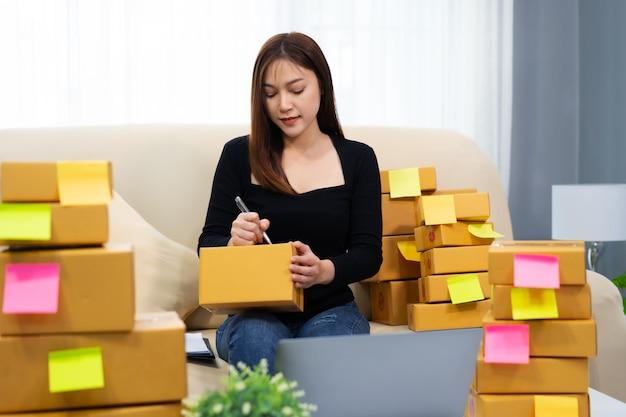 La donna imprenditrice che lavora con il computer portatile prepara le cassette dei pacchi per la consegna al cliente a casa