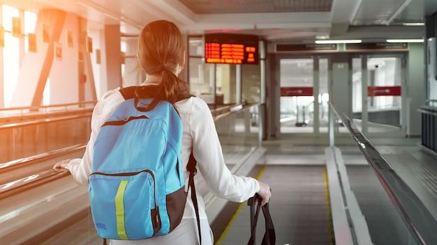 Donna su scala mobile con zaino e valigia nel terminal dell'aeroporto
