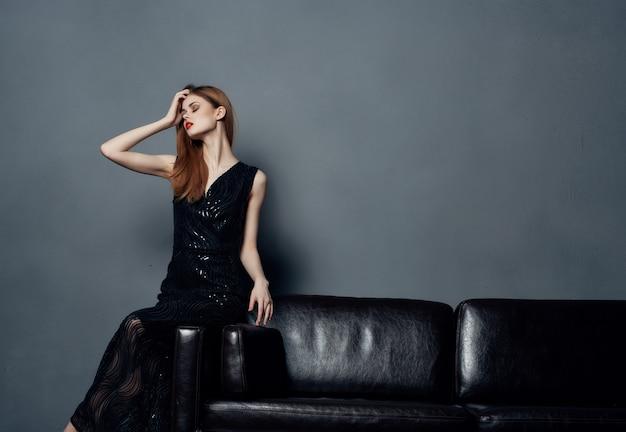 Donna in abito nero da sera seduta sul divano
