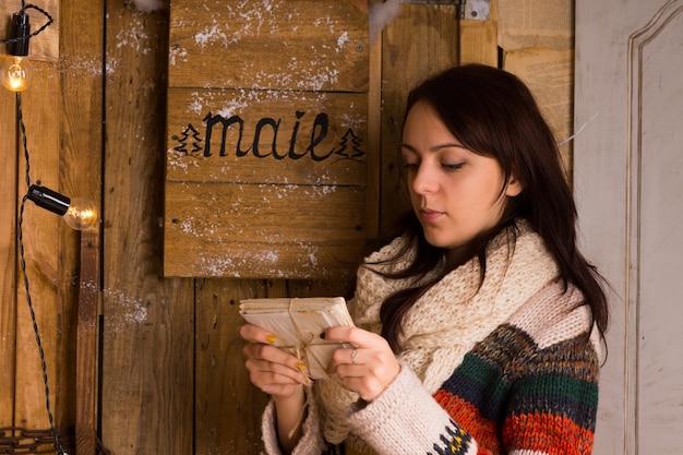Donna che esamina un fascio di lettere legate con uno spago dalla cassetta delle lettere con un'espressione contemplativa seria, vista laterale