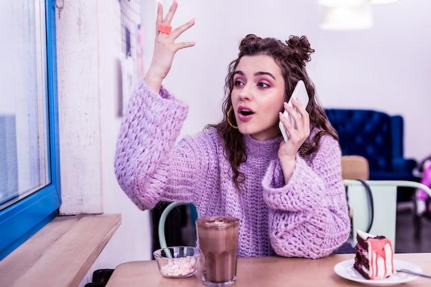 Donna che parla con entusiasmo. espressiva signora dai capelli lunghi gesticolando attivamente durante la conversazione pur avendo una torta al cioccolato nelle vicinanze