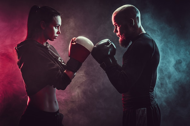 La donna che si esercita con l'istruttore alla lezione di pugilato e di autodifesa si guarda aggressivamente. mettiti di fronte.
