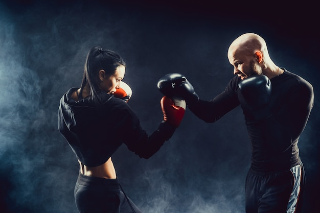 Donna che si esercita con l'istruttore alla lezione di boxe e di autodifesa lotta femminile e maschile