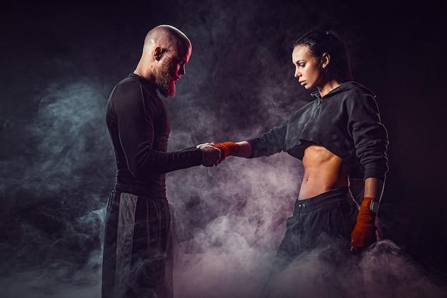 Donna che si esercita con il trainer alla lezione di boxe e autodifesa, studio, fumo nello spazio