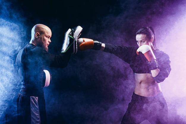 Donna che si esercita con il trainer alla lezione di boxe e autodifesa