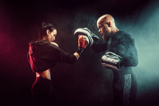 Donna che si esercita con l'istruttore alla lezione di boxe e dell'autodifesa