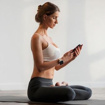 Donna che esercita yoga e che tiene smartphone